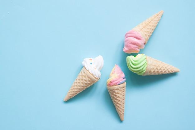 青い背景にアイスクリームの錐体のパステル調のメレンゲ