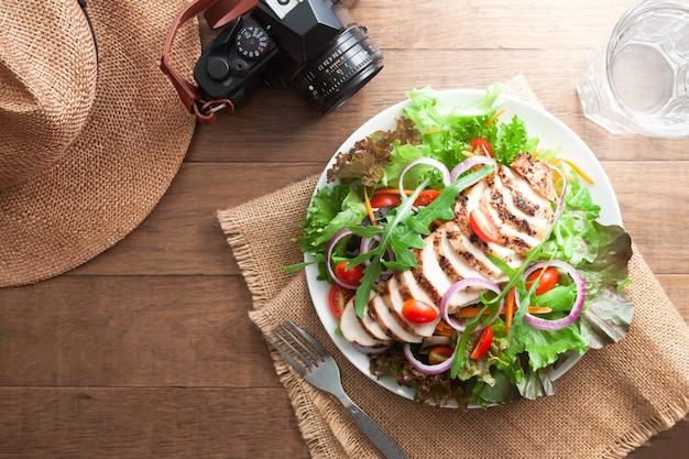 ヘルシーチキンサラダミックスグリーンと帽子とカメラを持つ木製のテーブルの上のトマト。健康