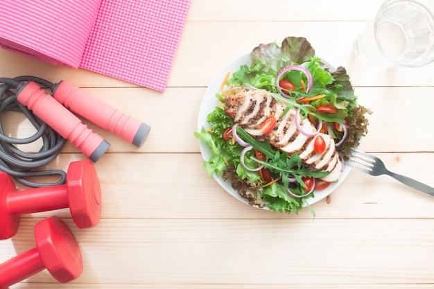 フラットレイアウトダイエットとフィットネスの概念。テーブルの上の健康的なサラダとフィットネス機器。