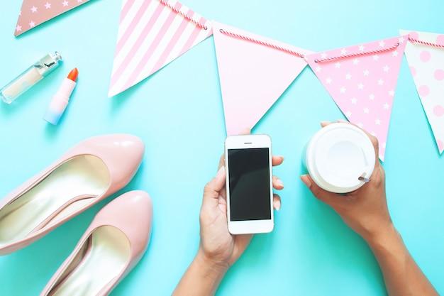 スマートフォンとパステルカラーのホオジロとコーヒーカップを持つ女性の手