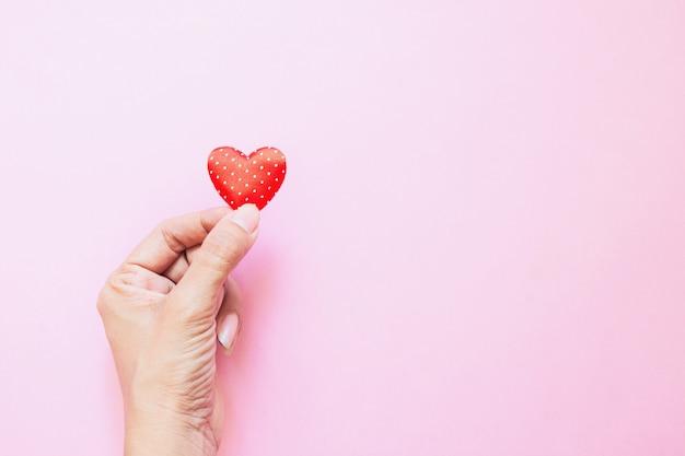 ミニ水玉模様の女の子の手はピンクの赤いハート。バレンタイン・デー。心の寄付愛の概念