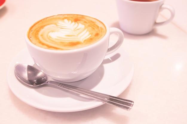 美しいカフェラテアートコーヒーと白いカップ。朝。さわやかなコンセプト