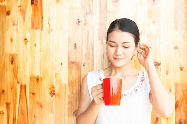 若くて美しいアジアの女性が赤カップを保持しています。幸せで健康な人