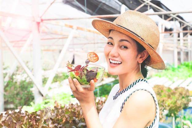 バックグラウンドで水耕栽培農場で野菜のサラダを食べる若いアジア女性