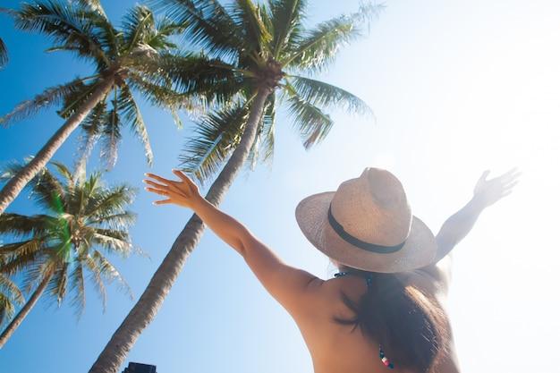 太陽の帽子を持つアジアの女性は、ヤシの木と空と腕を上げた。夏の旅行自由の概念