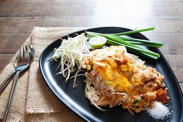 黒板の上にエビと卵でタイ焼きそばまたは焼きそば。タイ料理