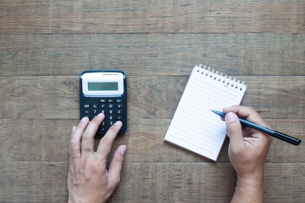 紙のノートと予算を計算する人間の手のフラットレイアウト。