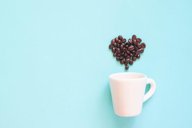 パステルカラーの背景にハート型に配置されたコーヒー豆と白いカップ