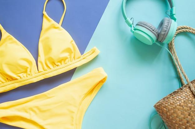夏のコレクション、黄色のビキニ、ヘッドフォン、そしてわらのビーチバッグ。夏休み