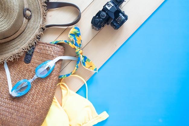 夏のアクセサリーと木製の床と青い色の背景上のカメラ。夏休み