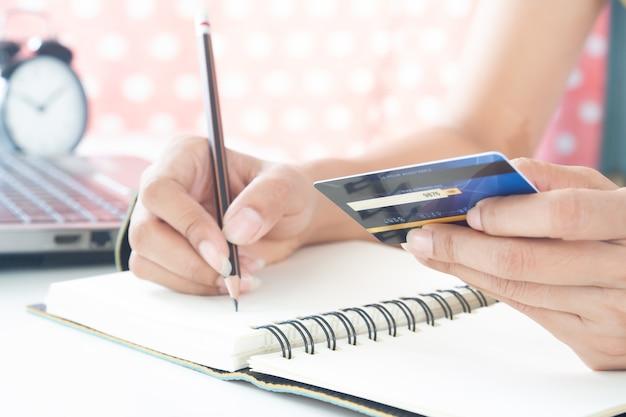 プラスチック製のクレジットカードを持つ女性の手。ビジネスと電子支払いの概念