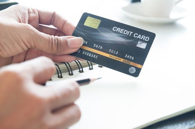 プラスチック製のクレジットカードを持っている手。電子決済、技術、オンラインショッピングのコンセプト