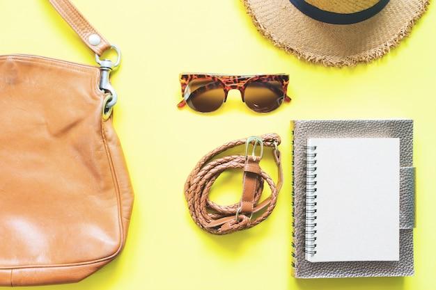 カジュアルな女性の服と黄色の背景に茶色のコンセプトのアクセサリー