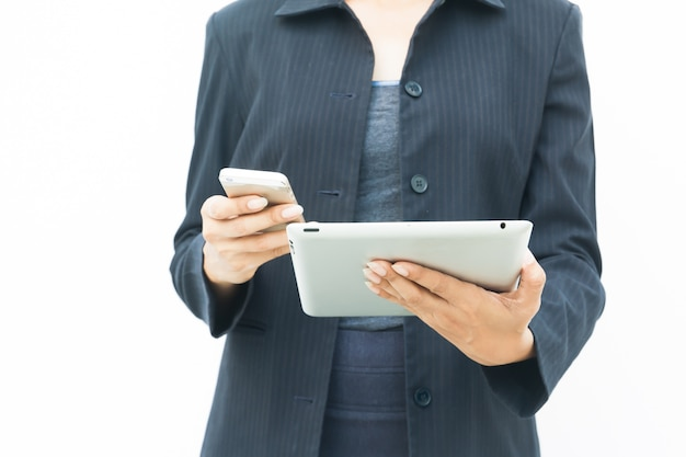 彼女のタブレットと携帯電話を使用して、白い背景にコピースペースとダークスーツのビジネスウーマン