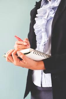 ビジネスの女性は、彼女のノートに書いているダークスーツで、ビジネスコンセプトはコピースペース