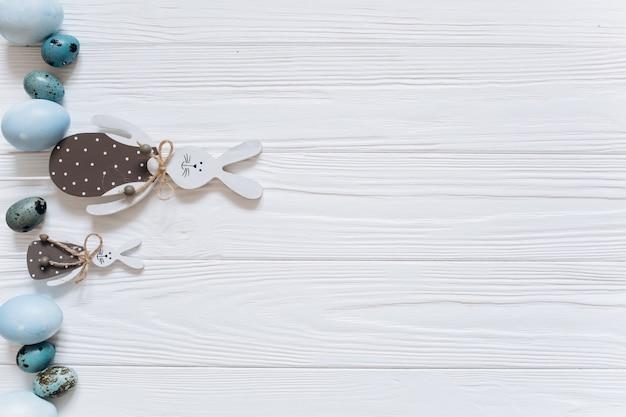 イースターウサギ、青い卵、白い木製の背景に雪滴。