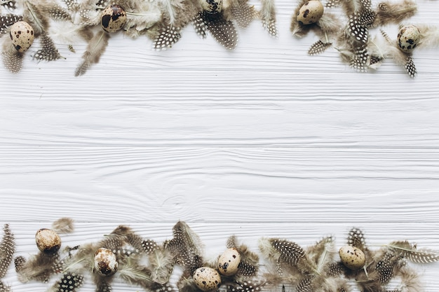 ハッピーイースターのための巣の中のウズラの卵と羽と木製のテキスト