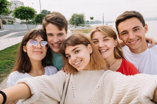 Лучшие друзья, берущие себя на открытом воздухе с подсветкой - счастливая концепция дружбы с подростком