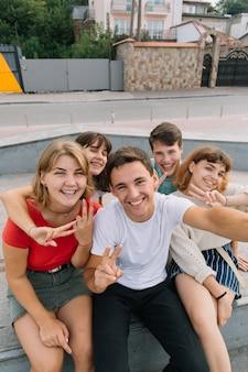 バックライト付きでセルフを屋外に撮っているベストフレンド - 十代の若者との楽しい友情のコンセプト