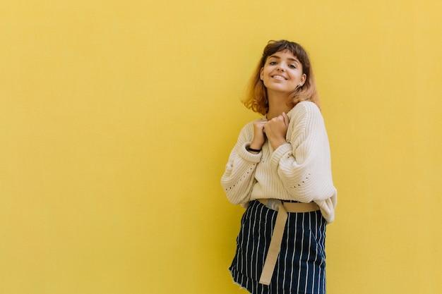 黄色の背景に対して単独で立っている間、長い縮毛で若いラテン系の女の子を笑います。