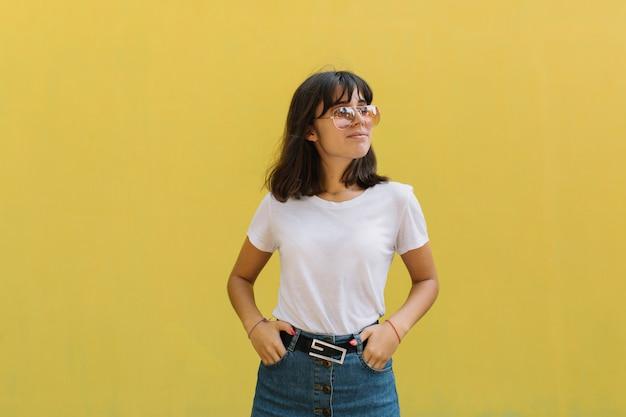 黄色の背景に対して単独で立っている間、眼鏡と中括弧で若い女の子を笑っている。