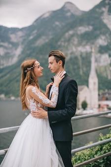 美しい結婚式のカップルは、妖精のオーストリアの町の背景の古い大聖堂で歩く