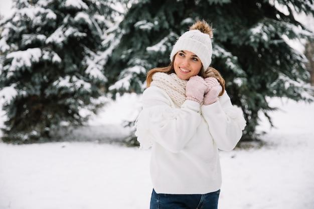 女性がクリスマスライト付きの公園でポーズします。冬の休日の概念