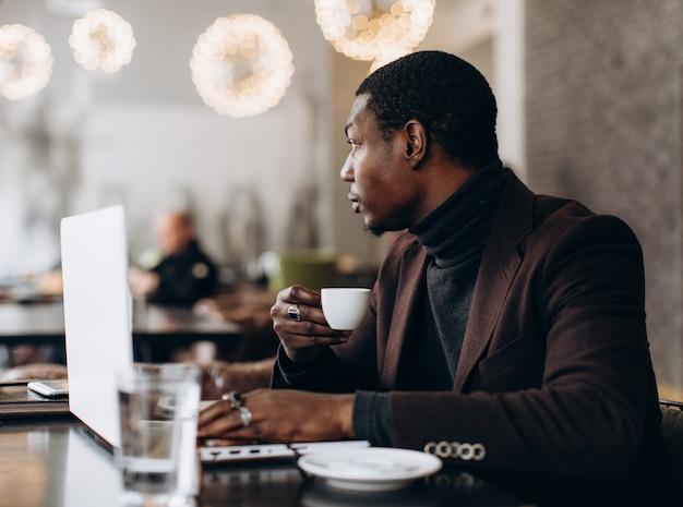 アフリカの実業家が電話を使用して、レストランでラップトップに取り組んでいる間コーヒーを飲みます。