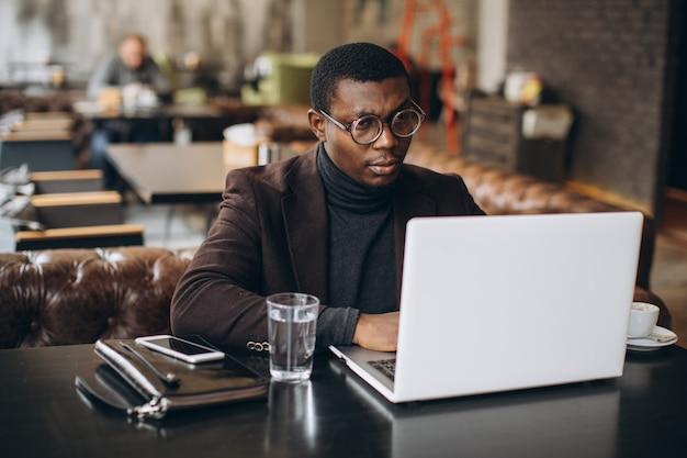 レストランでラップトップに取り組んでいる間携帯電話を使用して幸せなアフリカの実業家の肖像画。
