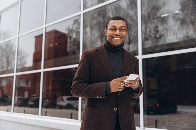 Афро-портрет красивый афро-американский бизнесмен с помощью смартфона.