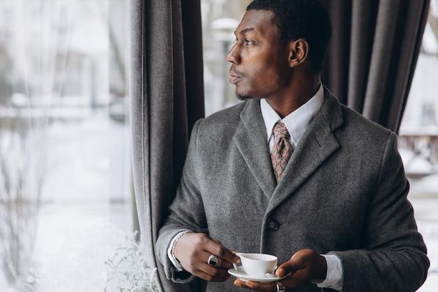 現代のアフリカ系アメリカ人実業家がレストランで一杯のコーヒーを飲みます。