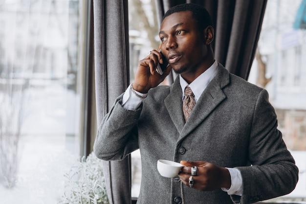 アフリカ系アメリカ人の実業家は、スマートフォンと一杯のコーヒーを飲みながらの会話があります。