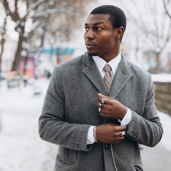 Афро-американский бизнесмен, используя смартфон в снежной зимой городской улице
