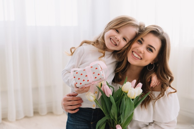 母の日おめでとう。子供の娘はお母さんを祝福し、彼女の花にチューリップと贈り物をします。