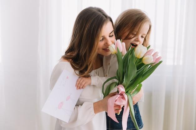С днем матери. дочь ребенка поздравляет мам и дарит ей открытку и цветы тюльпанов.