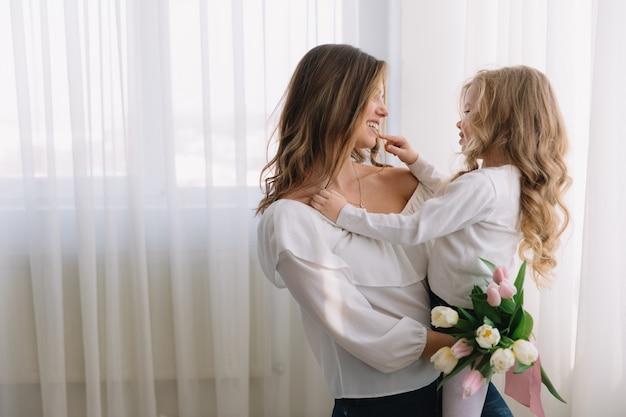 母の日おめでとう。子供の娘はお母さんを祝福し、彼女の花チューリップを与えます。