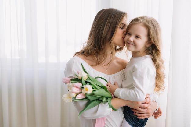 С днем матери. дочь ребенка поздравляет мам и дарит ей цветы тюльпанов.