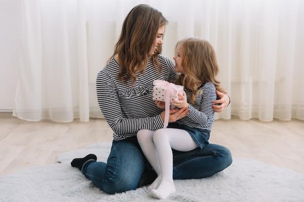 С днем матери. дочь ребенка поздравляет мам и дарит ей подарок.