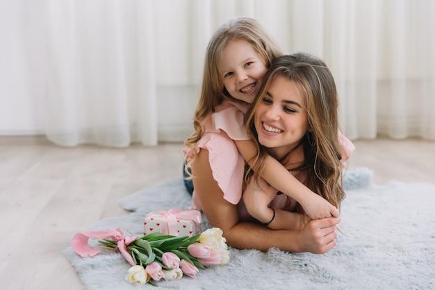 母の日おめでとう。子供の娘はお母さんを祝福し、彼女の花にチューリップとギフトを贈ります
