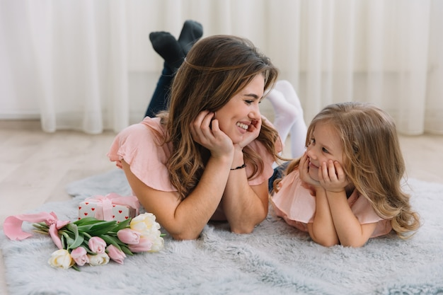 С днем матери. маленькая дочка поздравляет маму и дарит ей цветы тюльпаны и подарок
