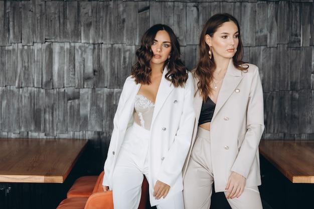 Две стильные сексуальные гламурные элегантные женщины носят белые костюмы в ресторане.