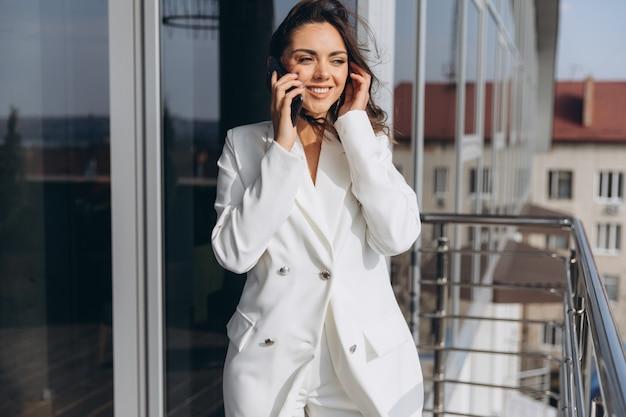 かなりスタイリッシュなビジネス女性は近代的なオフィスの近くのバルコニーに立っているとスマートフォンで話しています。