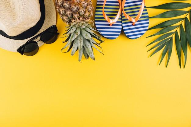 Летняя квартира заложить фон. пальмовые листья, шлепанцы, ананас, солнцезащитные очки и соломенная шляпа на желтом фоне.