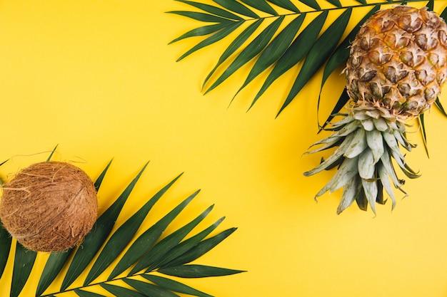 夏フラットレイアウトの背景。ヤシの葉、パイナップル、黄色の背景にココナッツ。