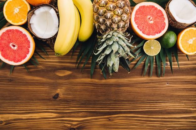 夏の果物熱帯のヤシの葉、パイナップル、ココナッツ、グレープフルーツ、オレンジ、木製の背景にバナナ。
