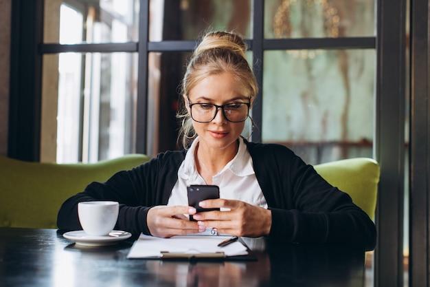 Блондинка деловая женщина сидит на рабочем месте и с помощью ноутбука в офисе, она смотрит на папку с документами, разговаривает по телефону и пить чашку кофе.