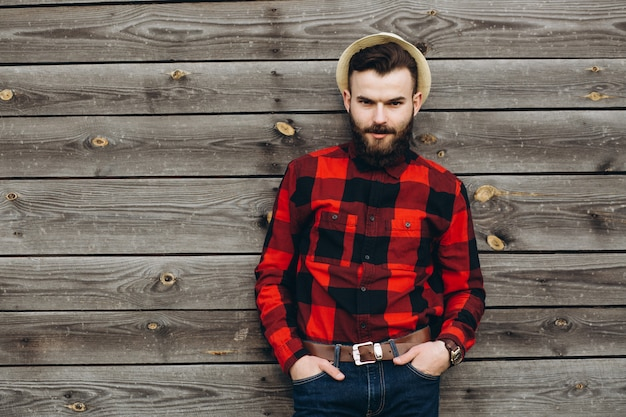 スタイリッシュなあごひげを生やした若い男の肖像は、ジーンズと赤いシャツで真の労働者黒にドレスアップ。