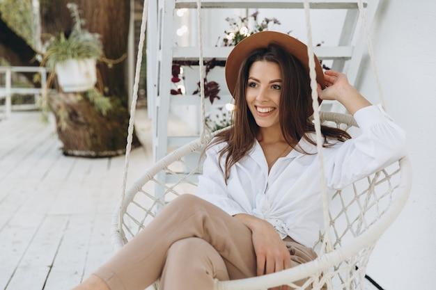 Стильная женщина улыбается и отдыхает в клубе на пляже в теплый летний день