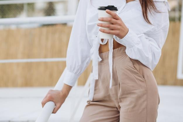 コーヒーを飲みながら夕日に暖かい夏の日のビーチフロントを歩いているスタイリッシュな女性