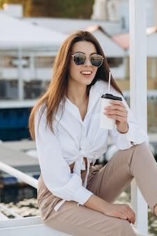Стильная женщина пьет кофе и гуляет по набережной в теплый летний день на закате